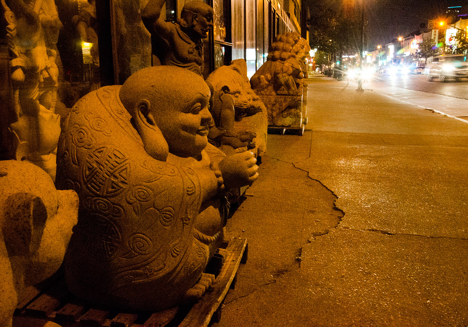 Small, stooped stone statues line a sidewalk.