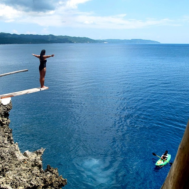 A girl stands on a diving board on the edge of a cliff, with her arms outstretched. The water is blue beneath her and a turquoise kayak is in the water.