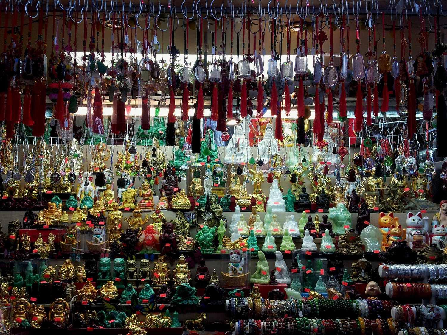 Lines of buddhas and other small statues in bright colors in a storefront.