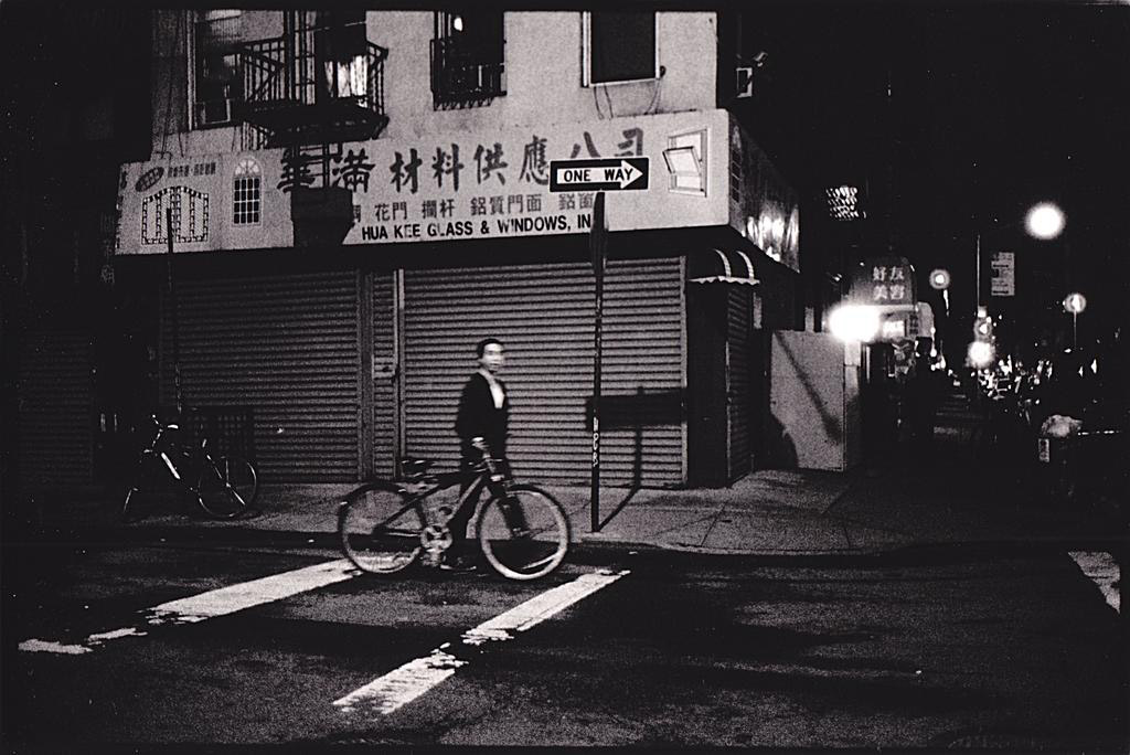 An intersection in a city. The storefront behind is written in Chinese. A man walks with his bike, faintly blurry because of the movement. It is night.