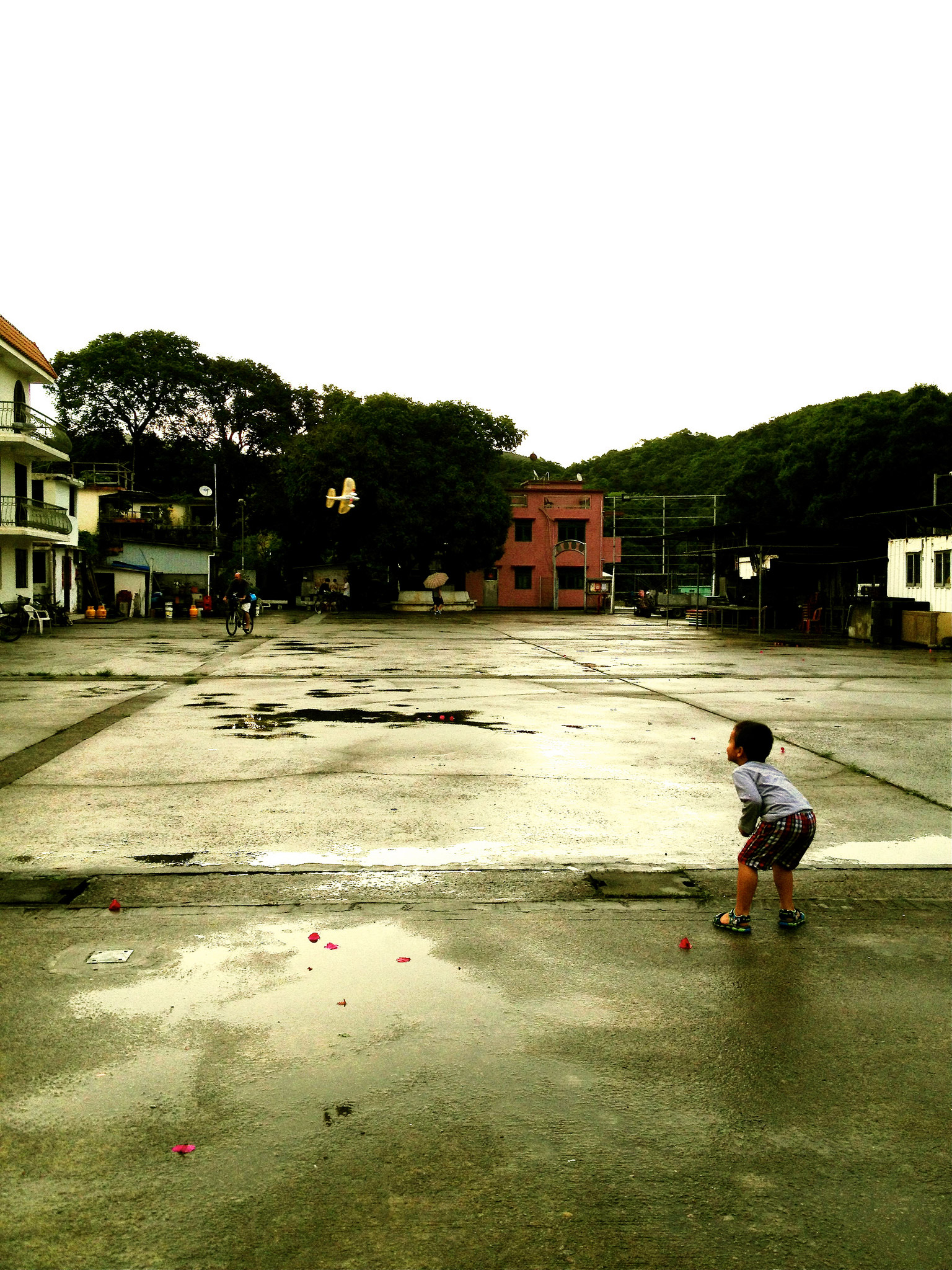 A little kid leans forward in a lot with puddles. A man rides a bike in the background. The lot is surrounded by houses and apartments.