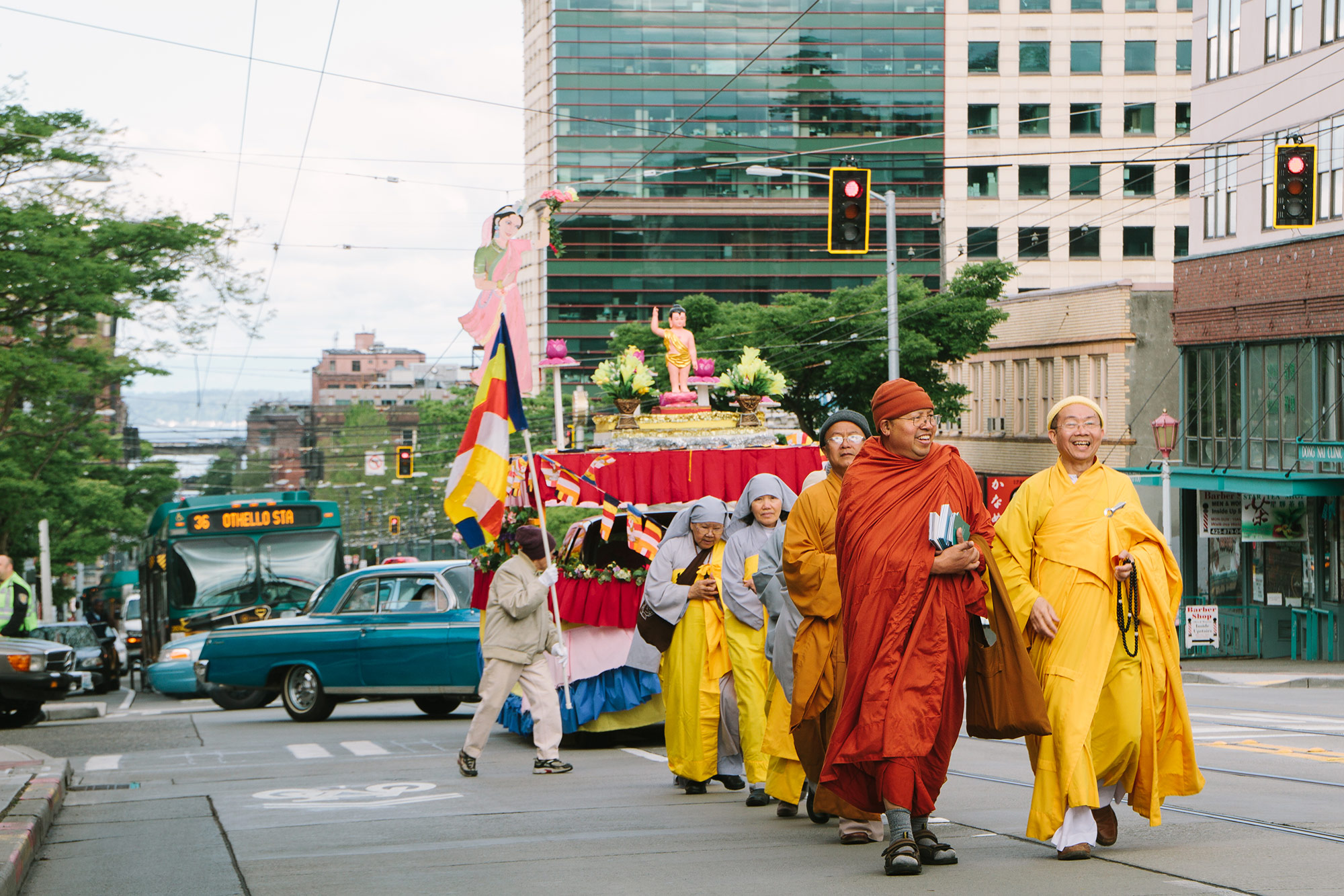 Monks walk down the street in front of a vehicle cked out in bright colors. In the background, a blue 62 impala falls into line behind them and a bus reads 36 Othello Sta.