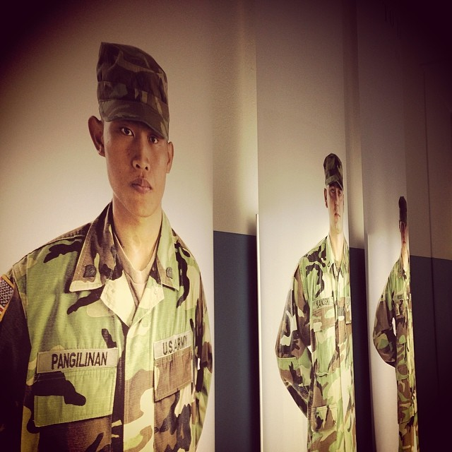 "large portraits of three soldiers in U.S. army uniforms looking straight ahead. The one closest to the front has a name tag that reads ""Pangilinan."""