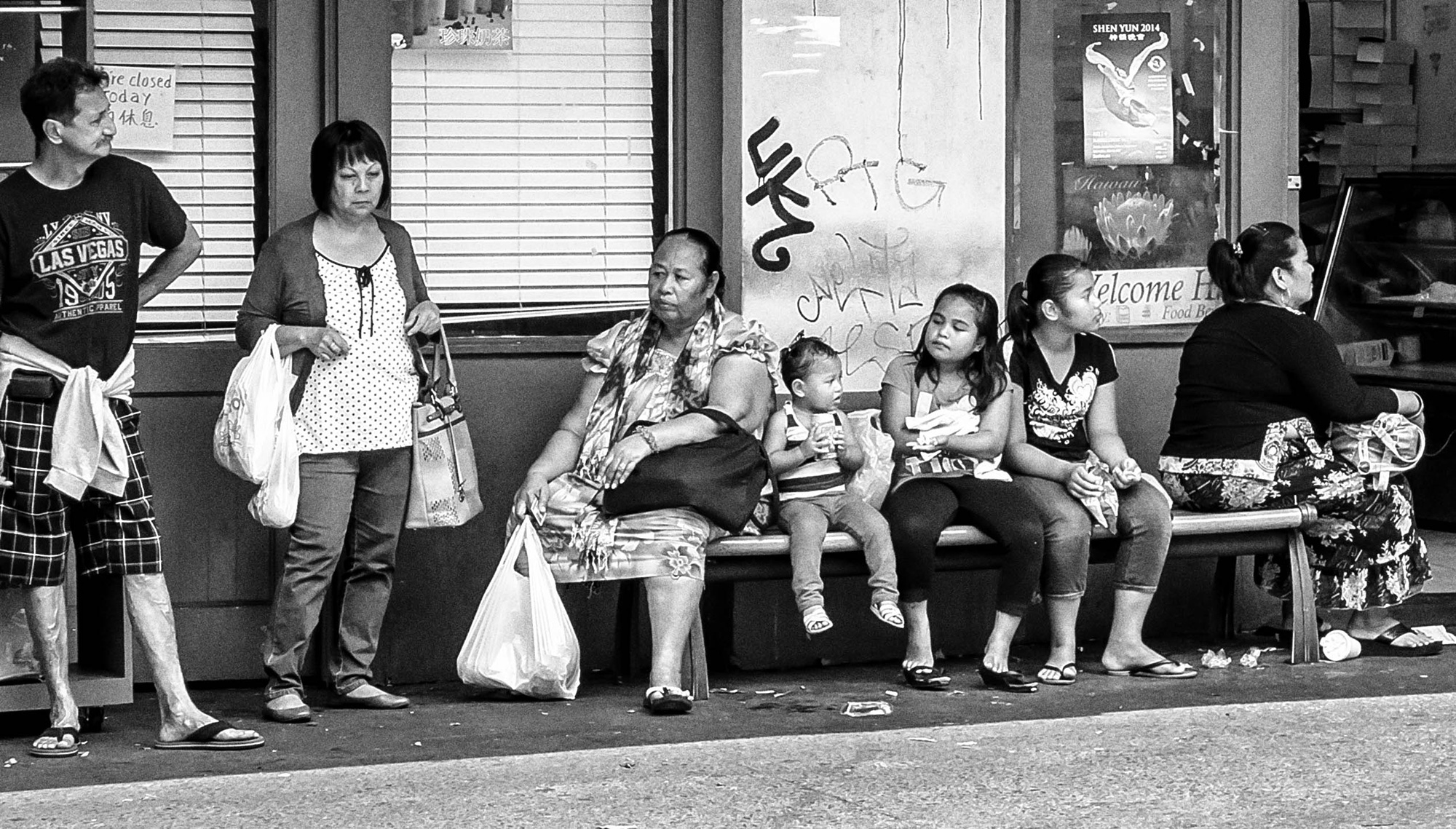A bench of people of all ages sit carrying shopping bags at what appears to be a bus stop.