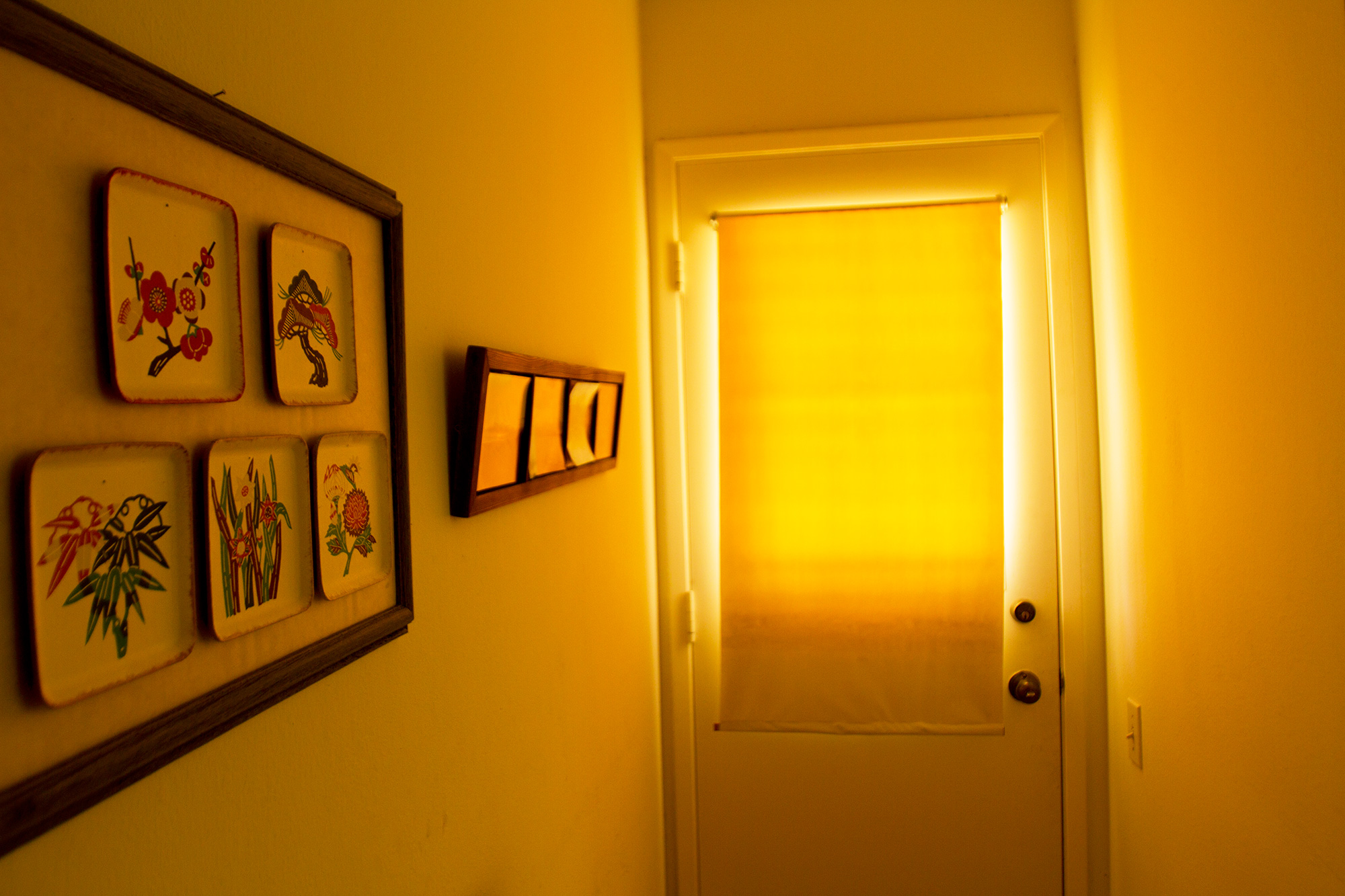 A hallway leading to a door with framed square plates with bamboo, cherry blossom and other nature-inspired designs. Bright light shows through a closed blind on the door, casting a yellow light over the hallway.