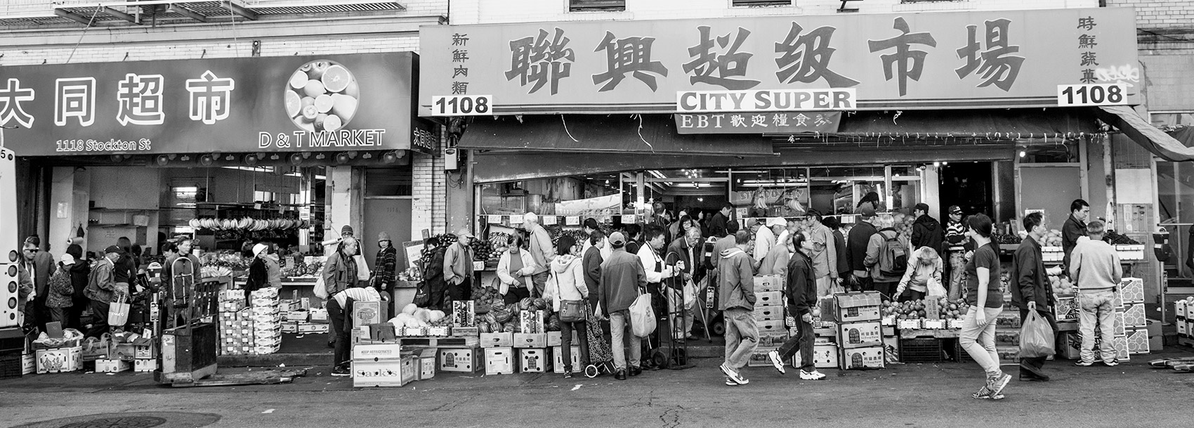 A crowd of people going in and out of City Super and D & T Market. The signs are written in Chinese and in English. Boxes line the store front.