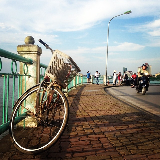 A bicycle left on a sidewalk on a bridge. The bridge overlooks water on the right, with a turquoise metal edge. A motorcycle drives by on the road.