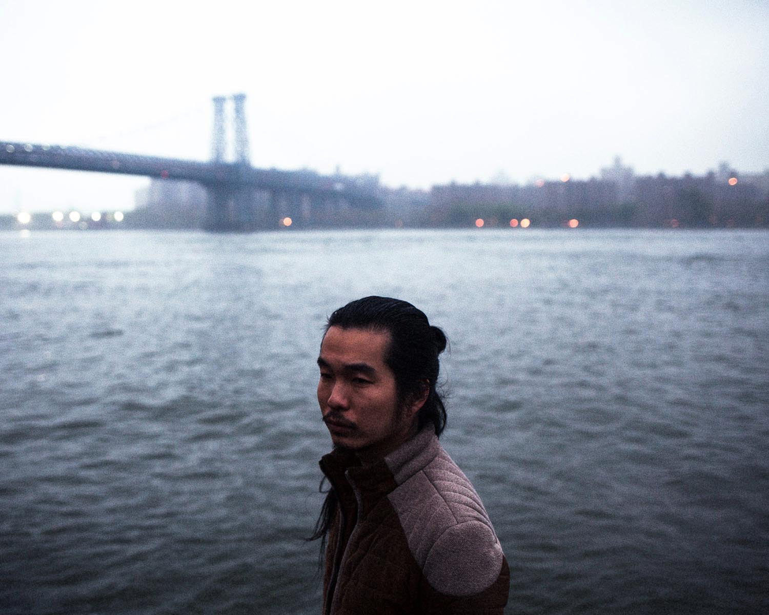 An Asian American man with a mustache and his hair in a bun stands in front of water. In the background a bridge crosses to the other side. There are buildings in the distance.