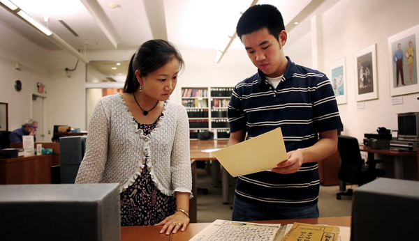 Summer 2010 intern Xiang Siow shows some findings he came across to staffer Noriko Sanefuji at the National Museum of American History's Archive Center.