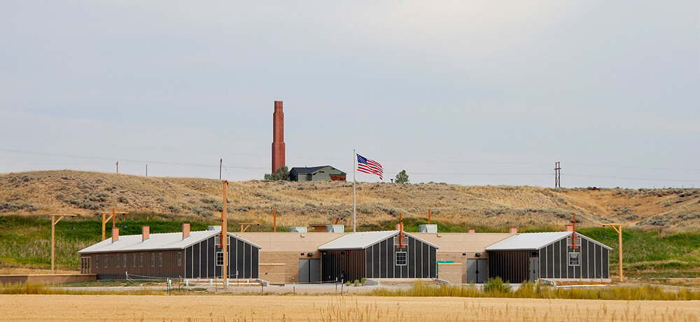 A view of the Heart Mountain Interpretive Center, built to look like three World War II Japanese American incarceration barracks. On a hill in the background, the old hospital building with its iconic red chimney overlooks the Interpretive Center.