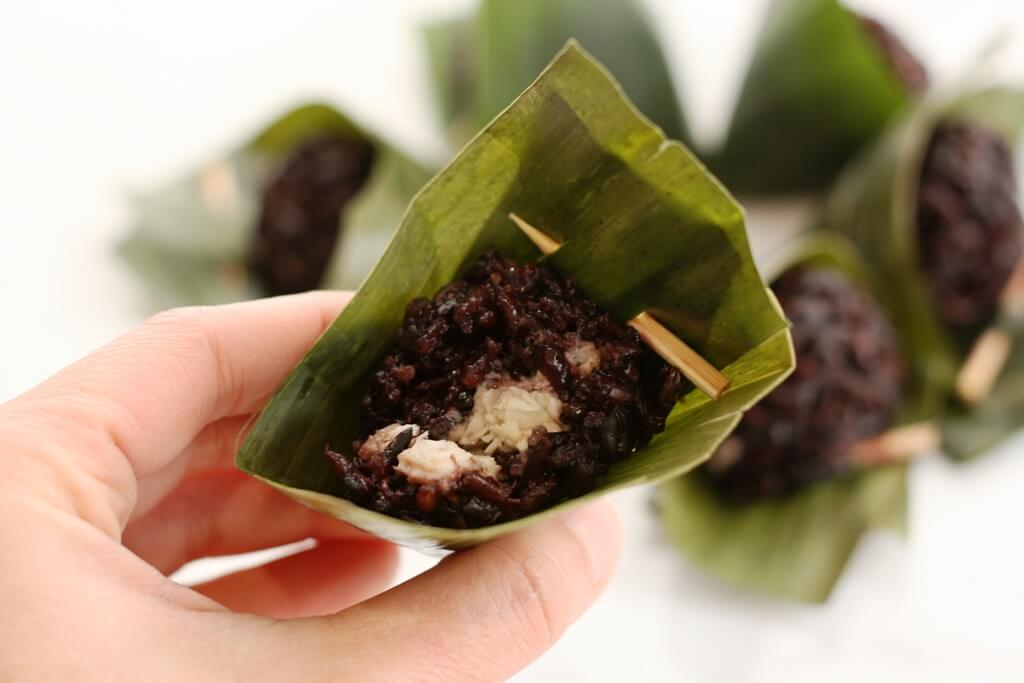 When you take a bite of this delicious dumpling, you'll be biting into a savory, spiced chicken filling wrapped with slightly sweet purple sticky rice imbued with the tealike flavor of banana leaves.