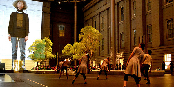 Dancers at the National Portrait Gallery's Kogod Courtyard dance in front of a projection of a middle-aged Asian American woman.