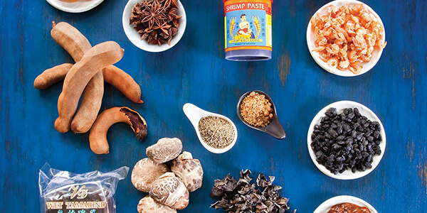 a photograph of different ingredients including shrimp paste, tamarind, anise, and more taken from above.